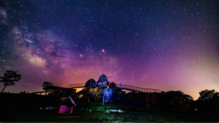 キャプチャ-3:大芝生広場の大型遊具の背景に広がる星々と天の川。